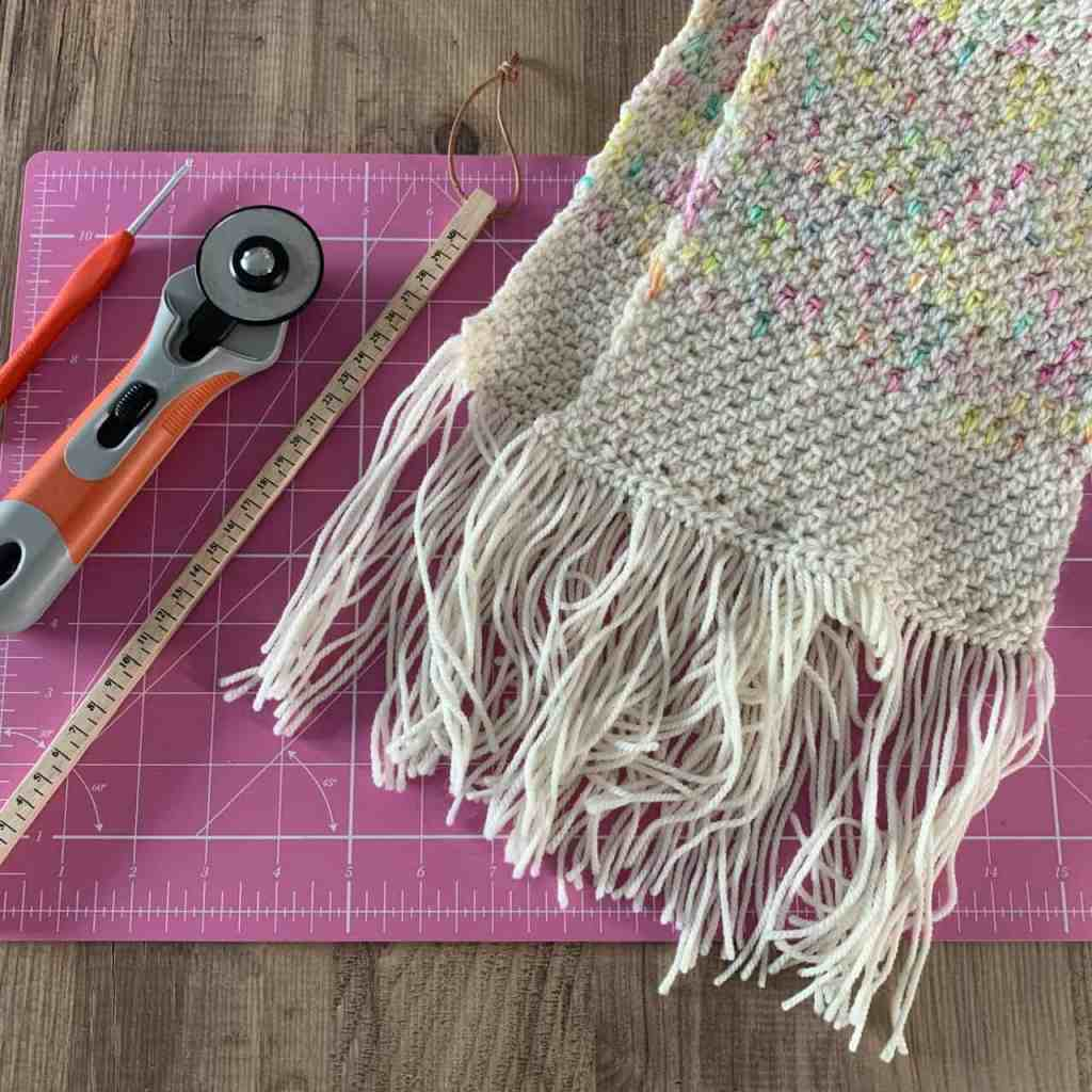 A scarf with a messy fringe lies on a pink cutting mat with a wooden ruler a rotary trimmer and a crochet hook ready to neaten it up