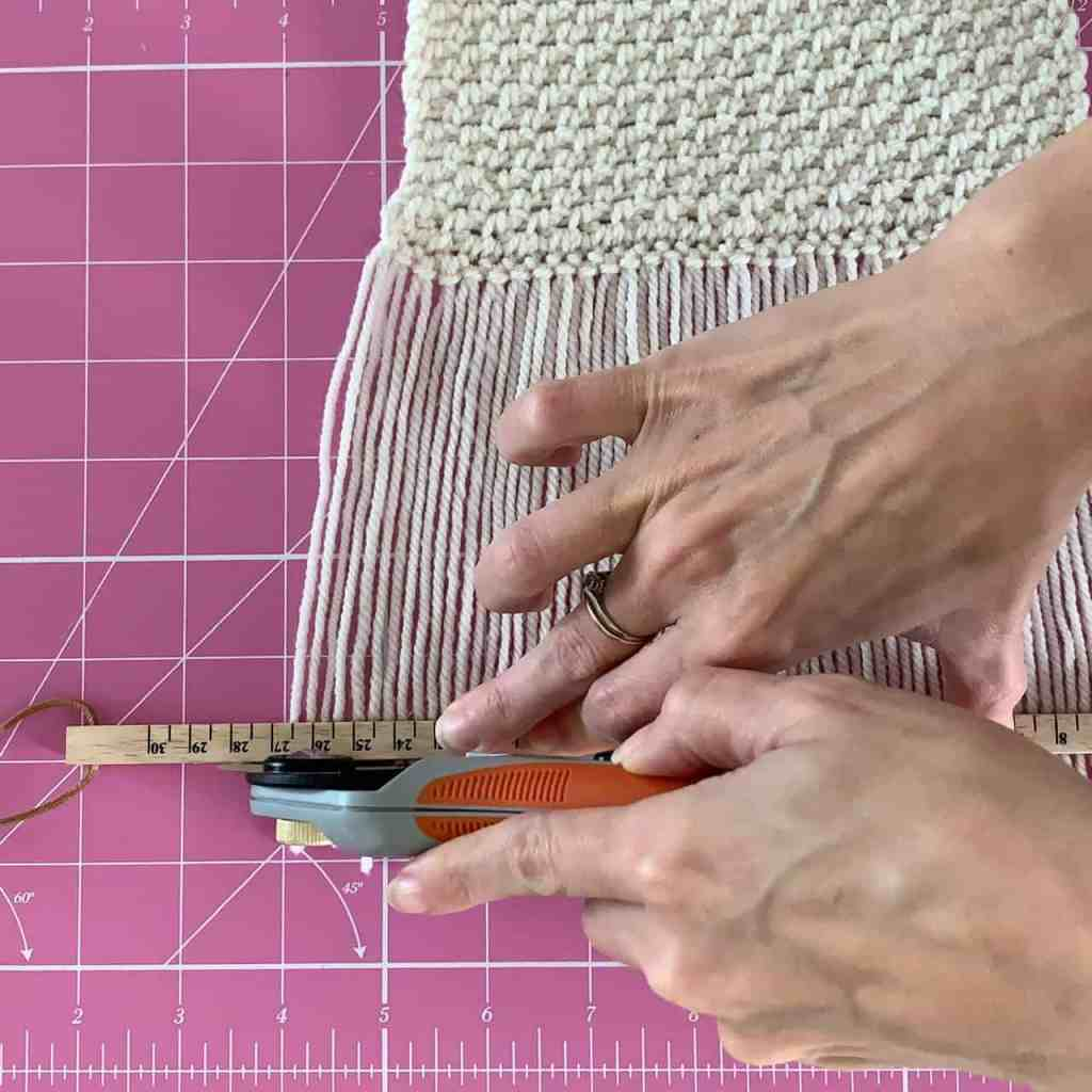 An action shot of a hand using a rotary trimmer running along a ruler edge to trim a yarn fringe