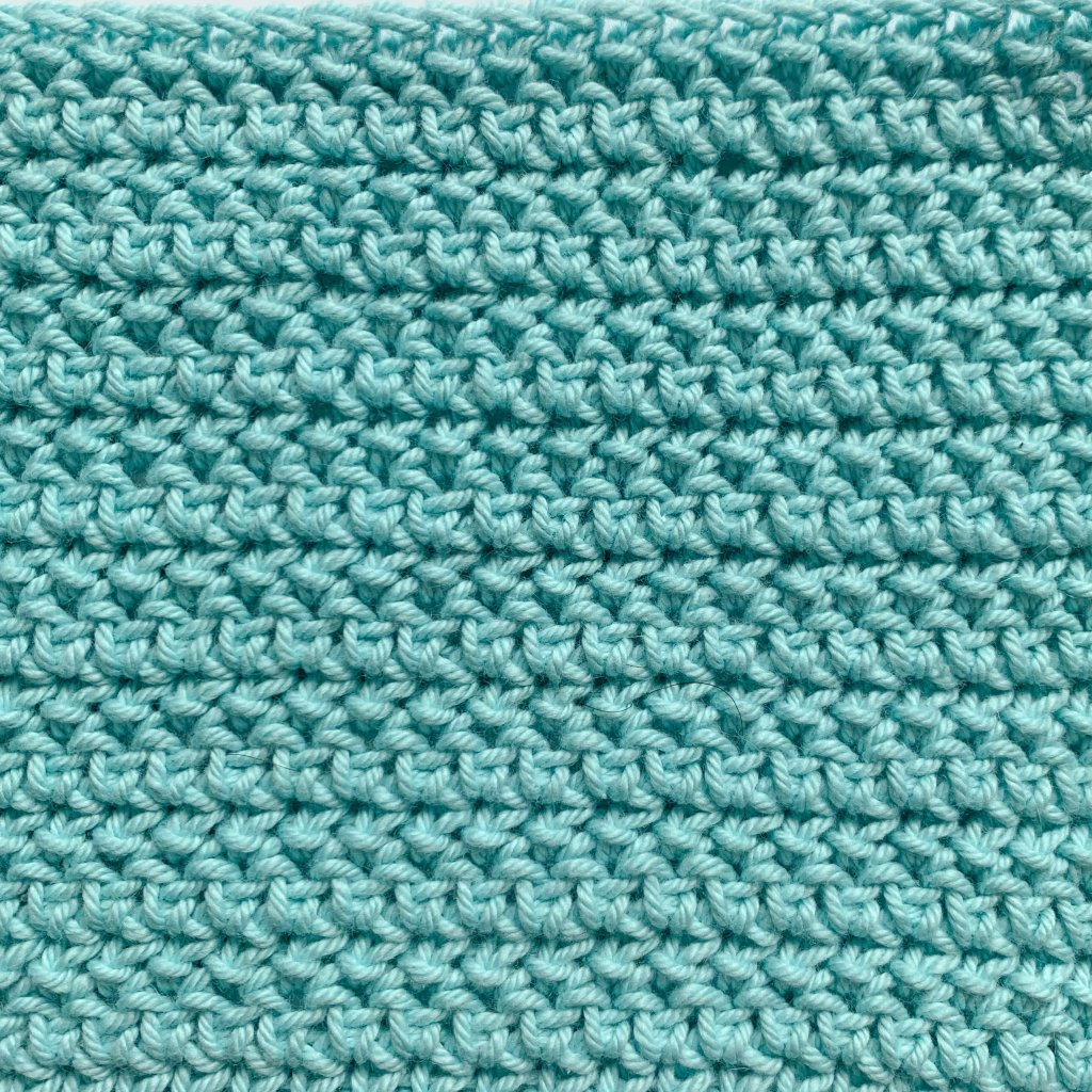 Close up of a herringbone half double crochet swatch in light turquoise