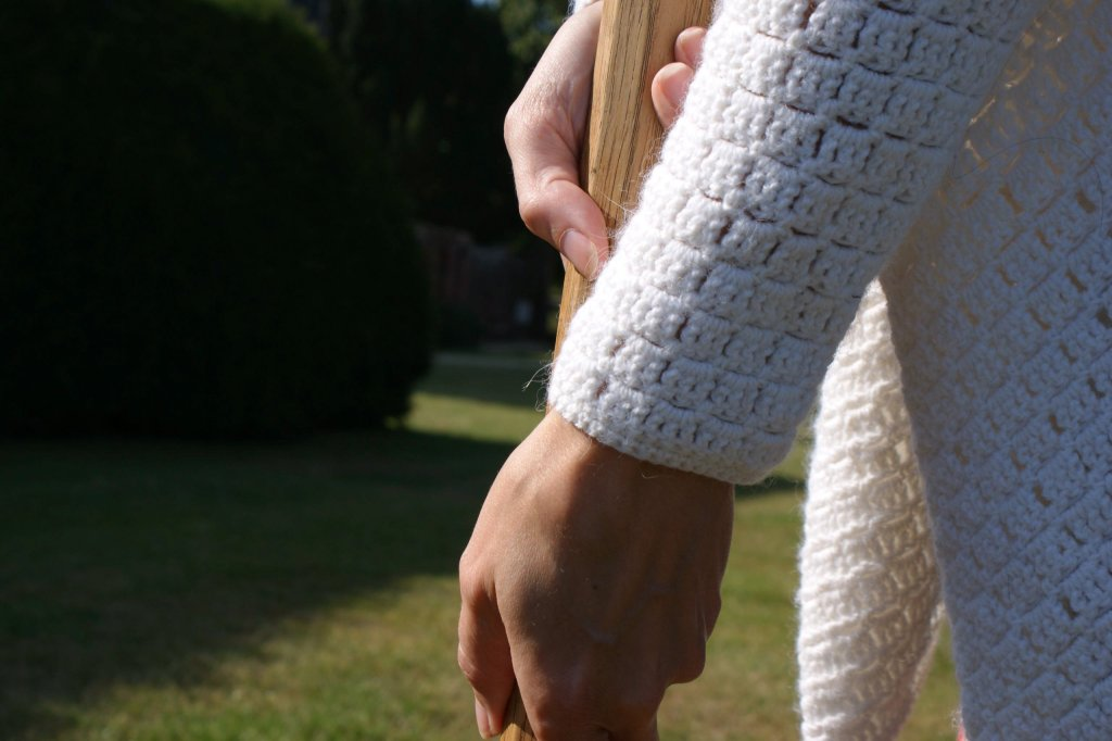 A close up of a woman holding a crochet mallet, wearing a crocheter cardigan, made with extended double crochet stitches