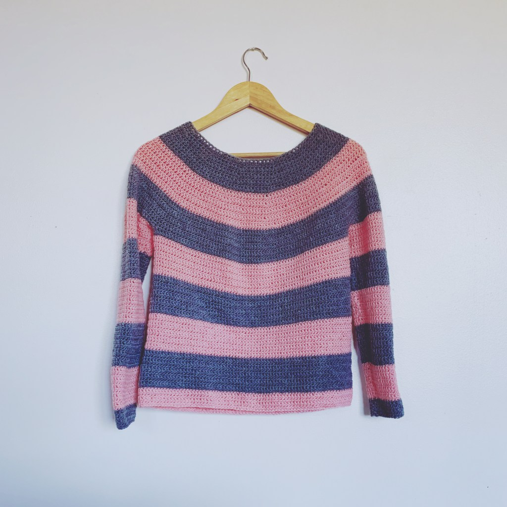 A 4ply pink and grey crochet striped sweater hangs on a white wall