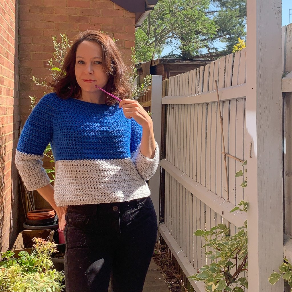 A woman models a blue and grey sweater in front of a walled garden