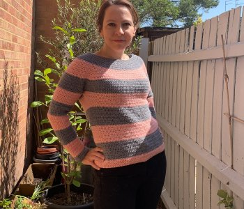 A woman stands in a small walled garden with hands on hips, smiling at camera wearing a crochet sweater she made