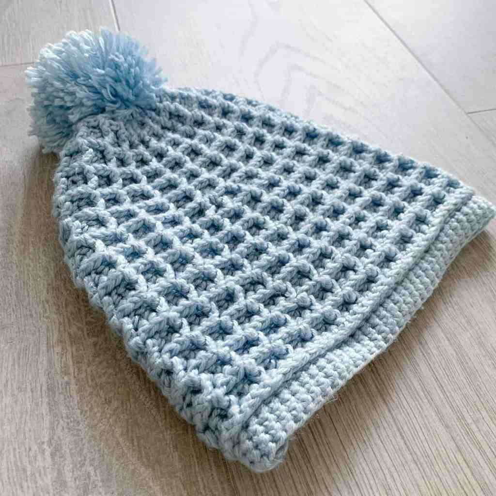 Waffle stitch hat with worse for wear pom pom