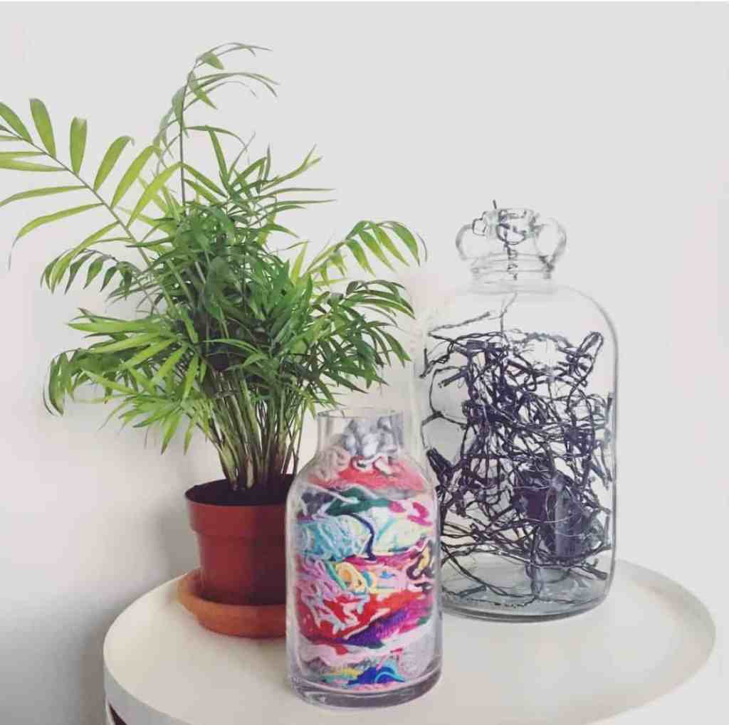 A jar full of yarn ends on a table next to a plant and jar of fairy lights