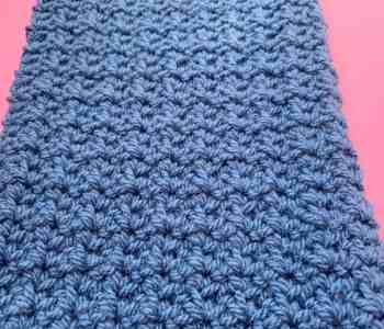 an angled landscape shot of crochet spider stitch made in blue yarn