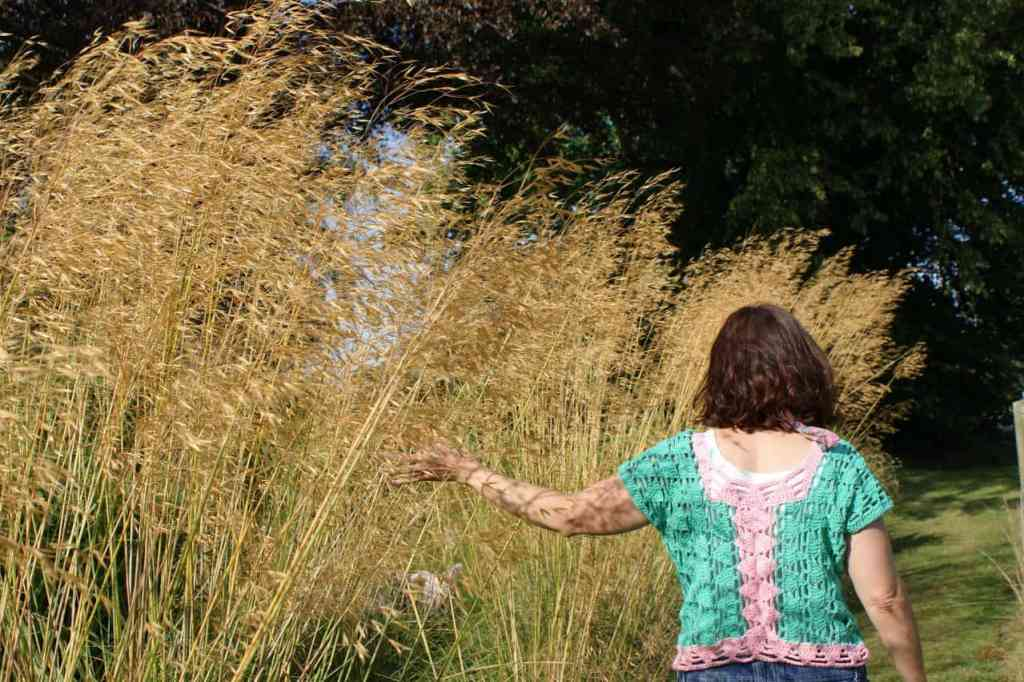 A woman in a crochet tee walks away from the camera on a sunny day with her hand brushing through tall grass