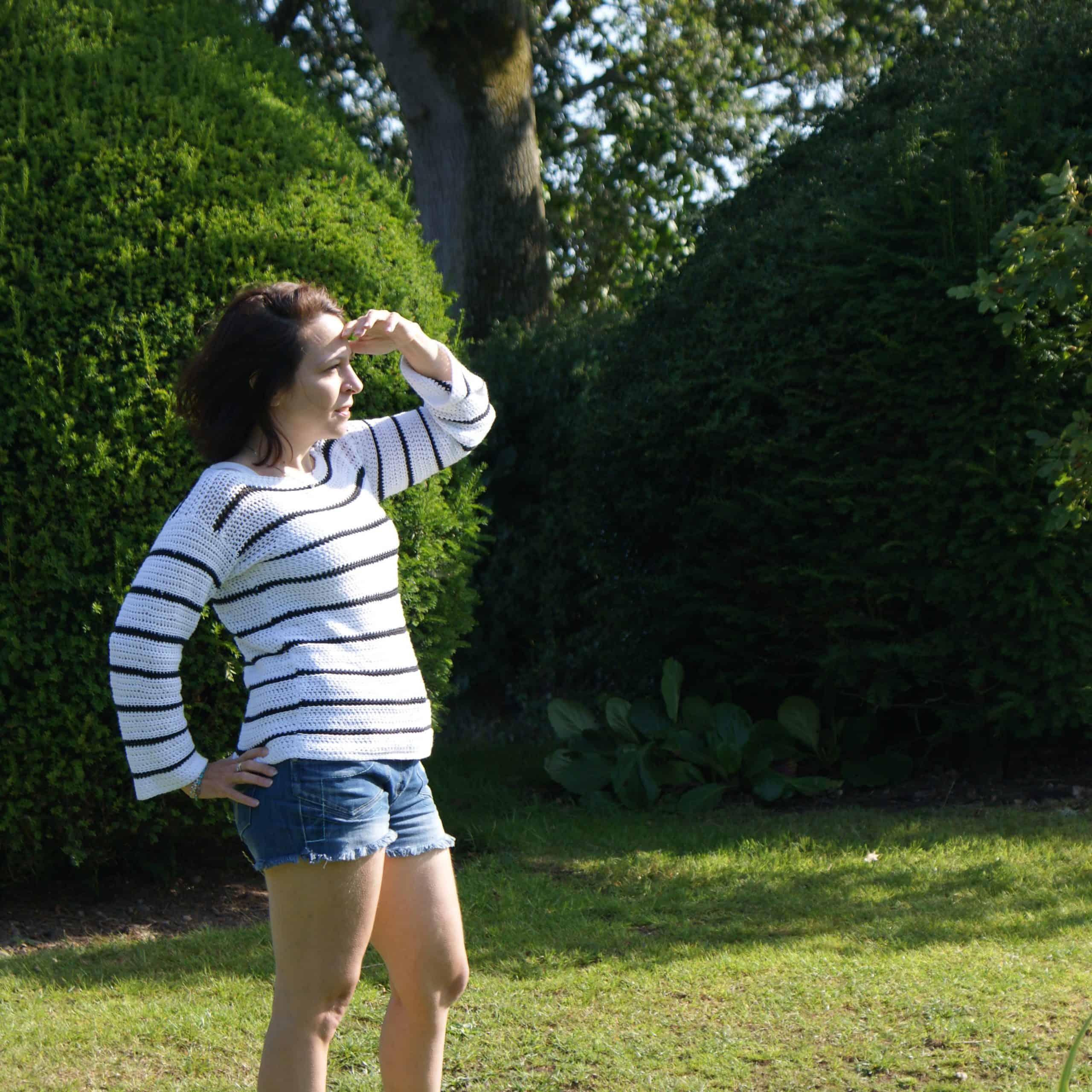 Woman in black and white striped crochet top stands in a garden shielding her eyes from the sin