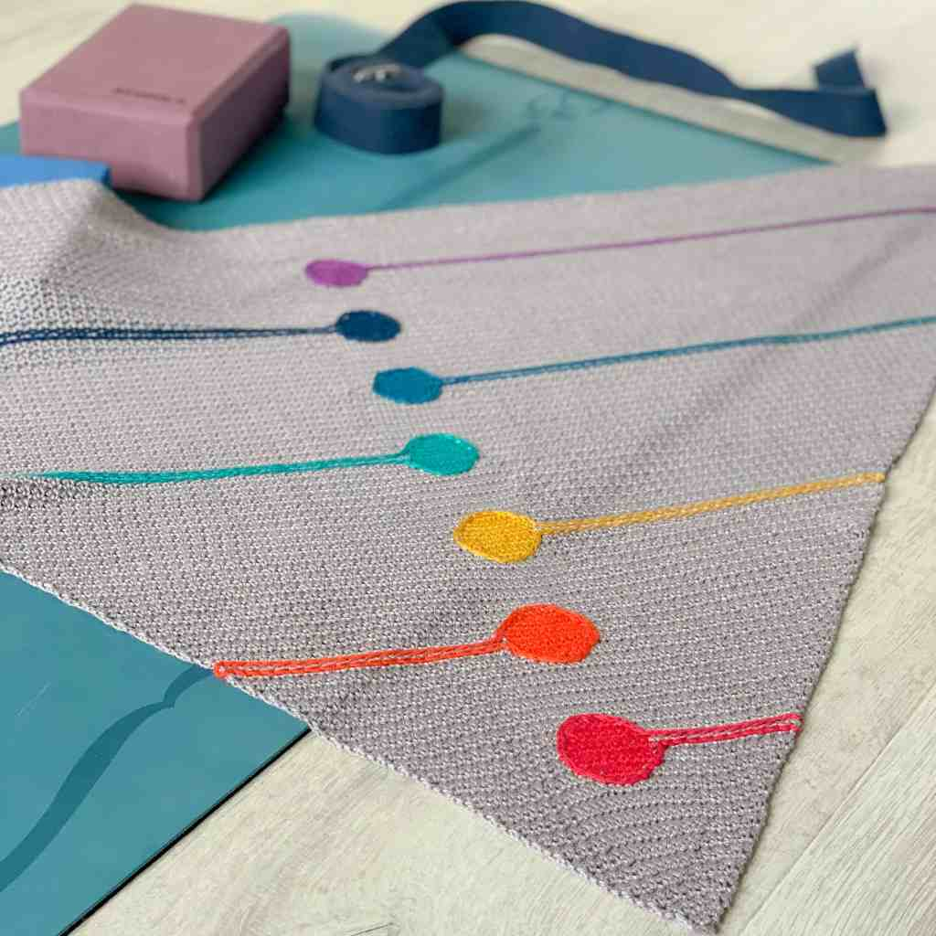 the chakra shawl draped over a yoga mat with yoga accessories in the background