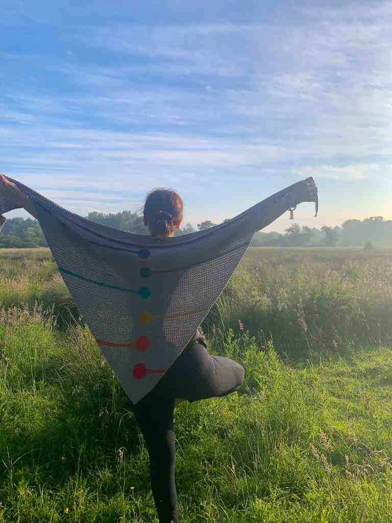 A woman stands with her back to the camera in tree pose staring at sunrise on a meadow holding out a chakra inspired crochet shawl