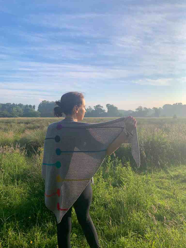 A woman stands with her back to the camera on a meadow staring at a sunrise, wrapped in a rainbow crochet shawl