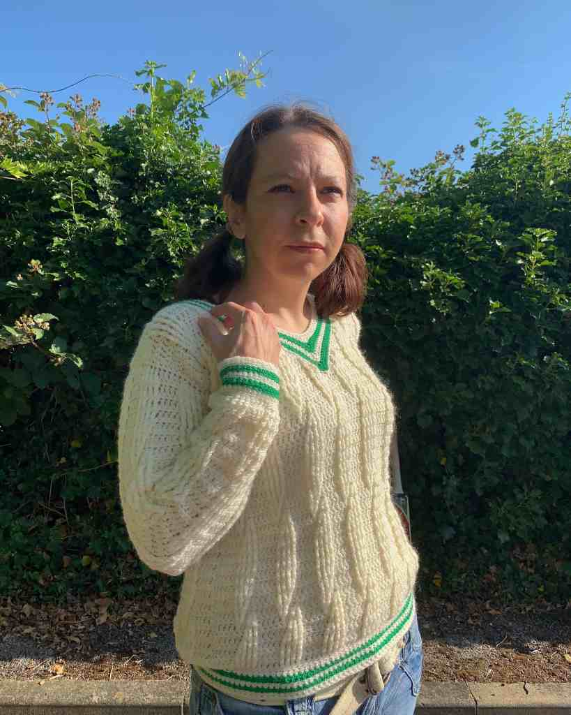 A woman wearing a cream cabled crochet sweater with green stripes on the v-neck hems and cuff bends her arm to her shoulder and looks beyond the camera