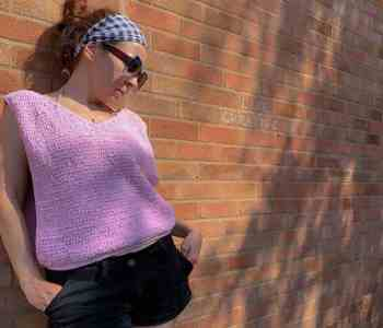 A woman wearing a pink crochet top leans against a brick wall