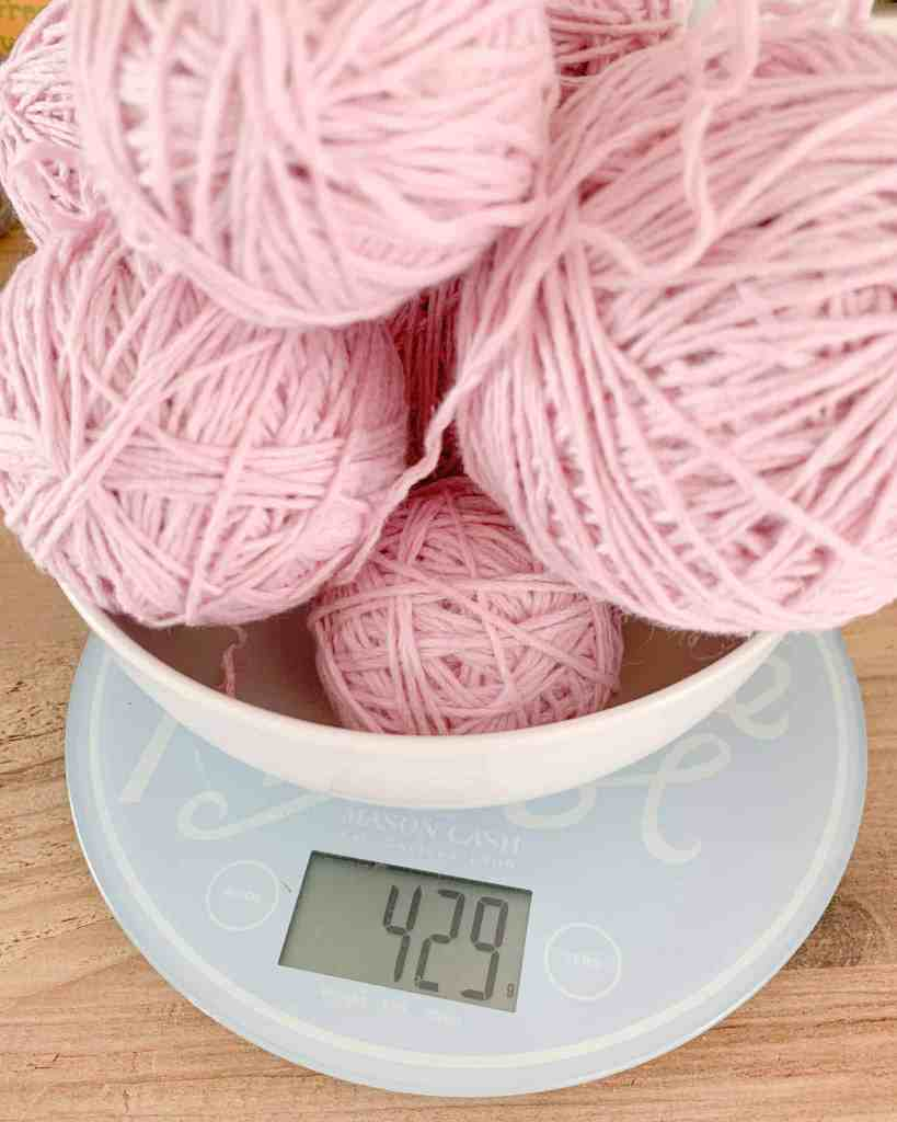 balls of yarn in a bowl, seen from above are placed on a scale which reads 429 grams