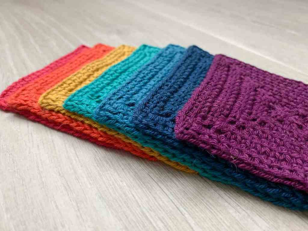 A rainbow of granny squares are laid out overlapping each other in a diagonal horizontal line