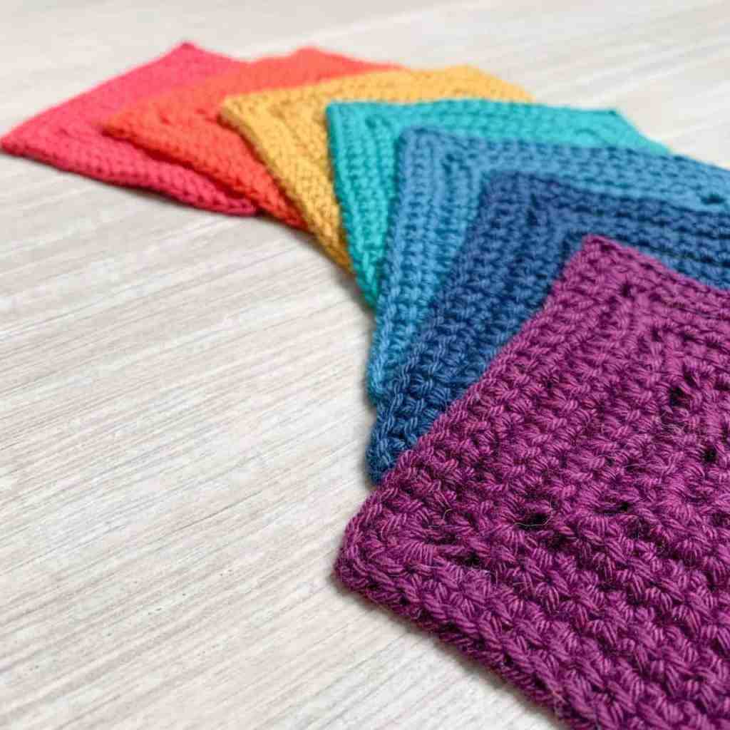 7 little love grannie squares one for each colour of the rainbow are laid flat overlapping in an ark