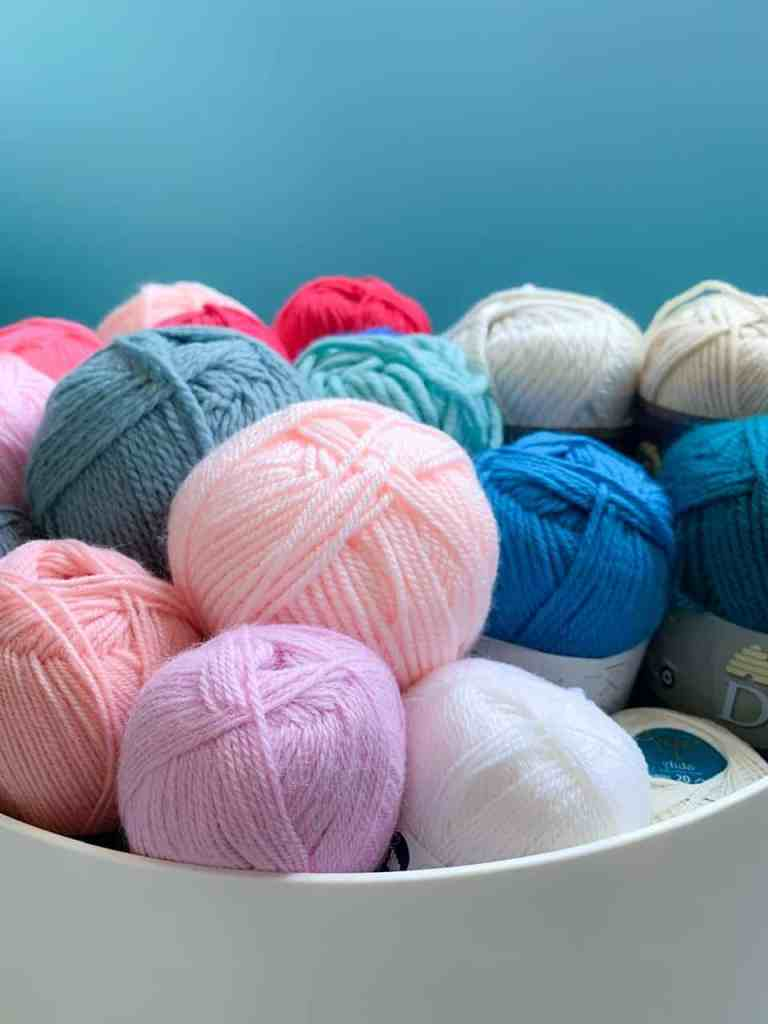 An assortment of blue pink and cream yarns with a blue background behind
