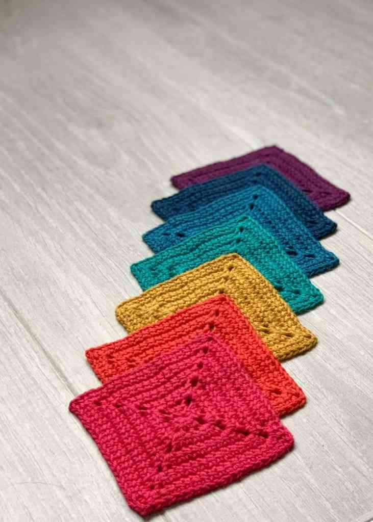 A rainbow of granny squares are laid out overlapping each other in a vertical line