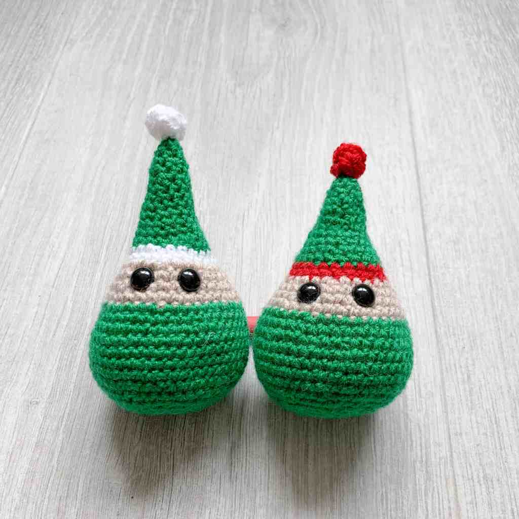 Two crochet elf decorations next to each other on a grey background, one smaller than the other