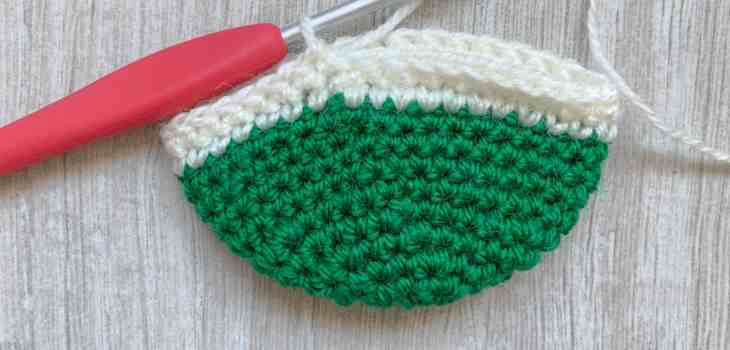 A green crochet half sphere with two rounds of cream crochet stitches made on top