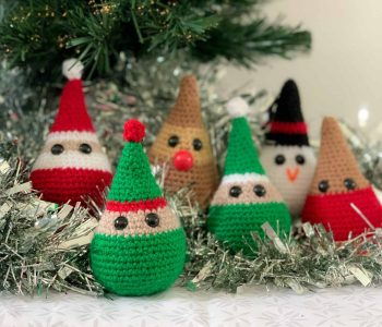 With a focus on the elf, 6 characterful crochet Christmas decorations (Santa, a robin, a reindeer, a snowman and two elves), sit on a white and grey patterned surface in front of the bottom of a Christmas tree with silver tinsel behind it