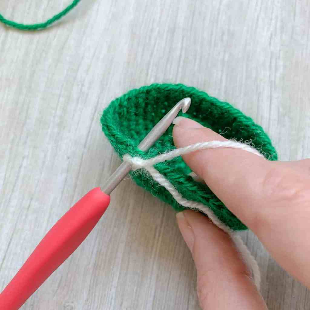A crochet hook with cream yarn on it is inverted into a round of green stitches