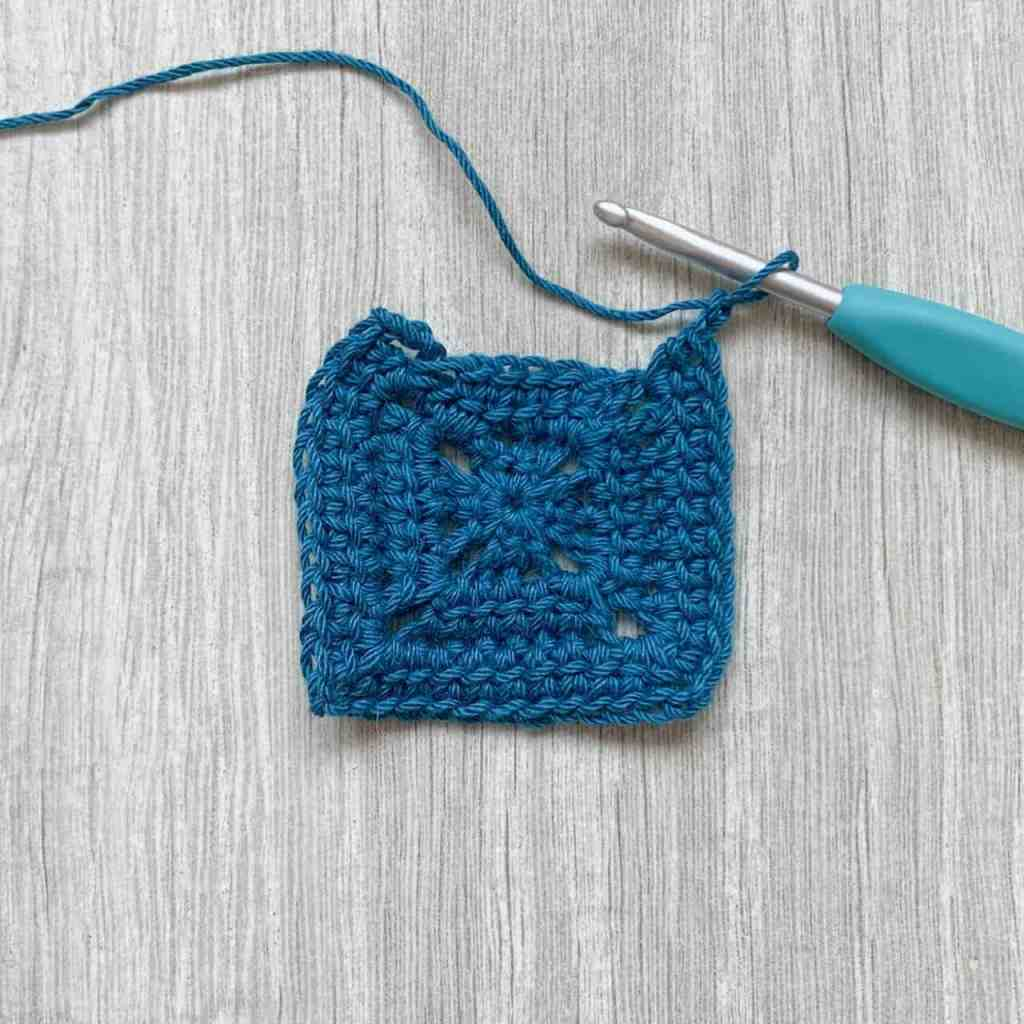 a progress shot of round 2 of a crochet square