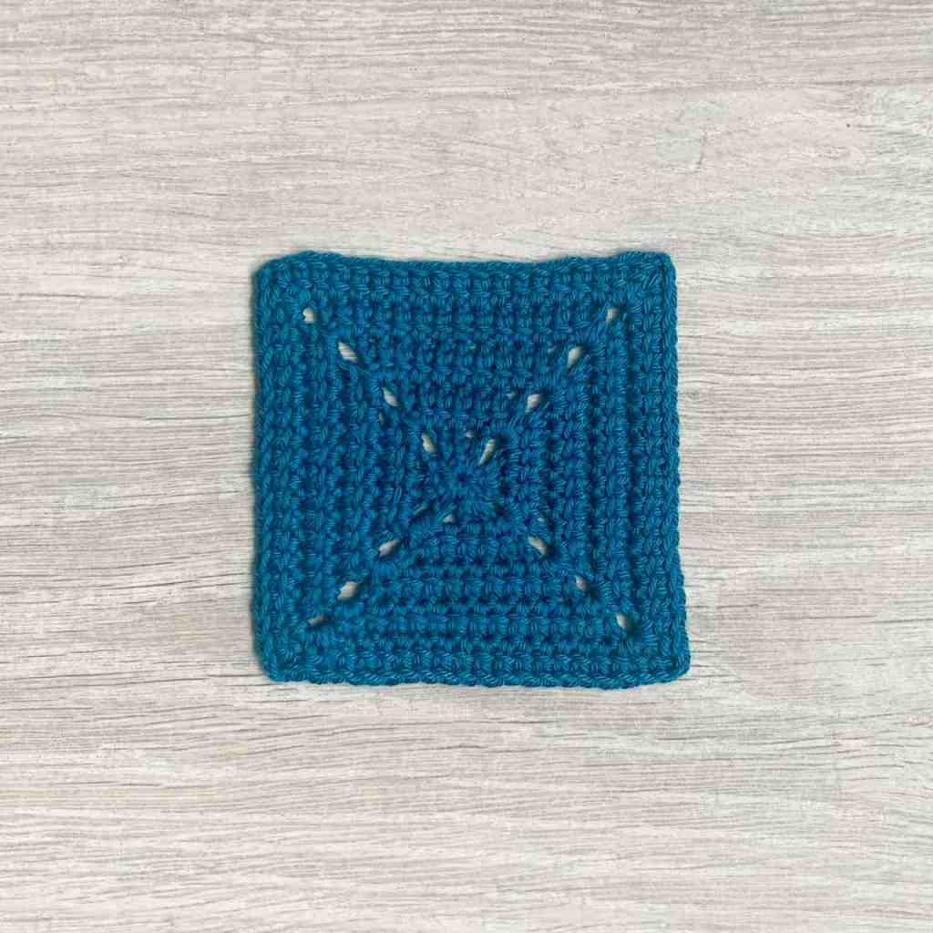 A blue solid linked double crochet granny square lays on a grey wood effect surface