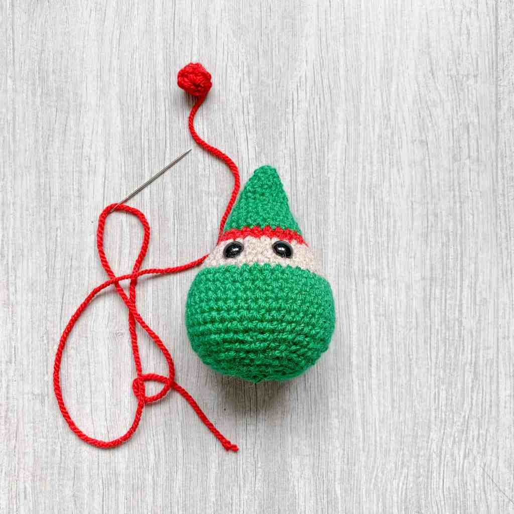 a crochet elf decoration with a red crochet bobble about to be attached to the top of it's head