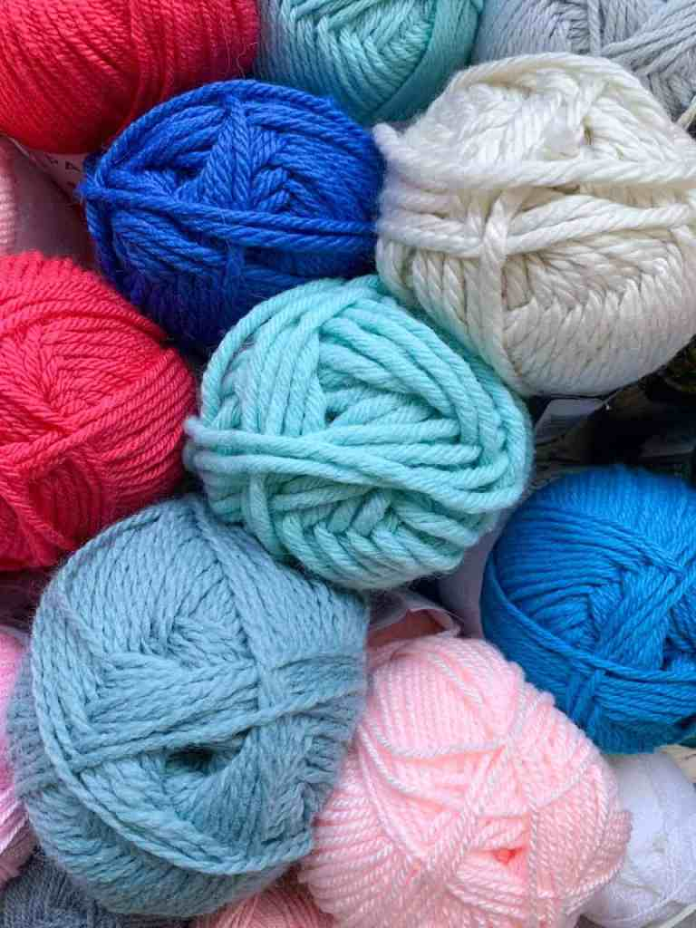 A view of yarn from the top, in different weights and blues, pinks creams and greys