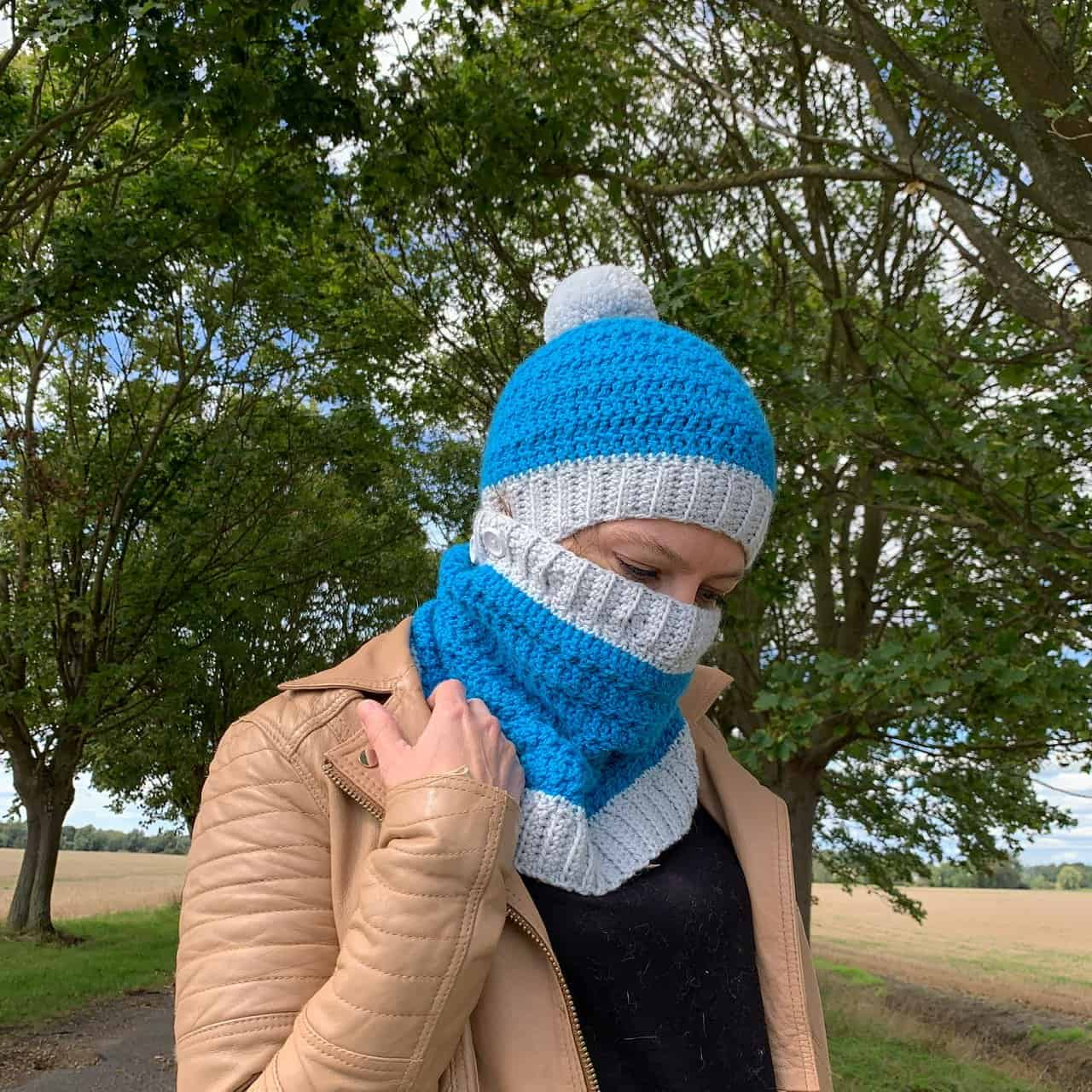 A woman stands in front of an avenue of trees in a turquoise hat and cowl that covers her face