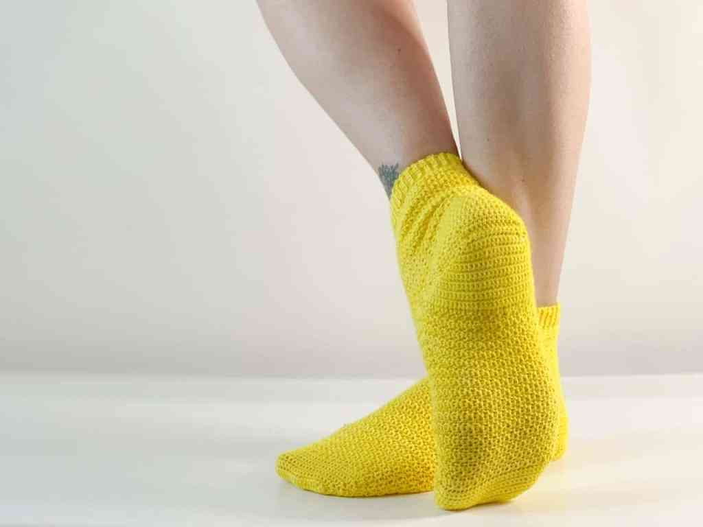 A pair of yellow crochet socks adorn a woman's feet. Her lower legs are crossed with the heel of one sock facing the camera