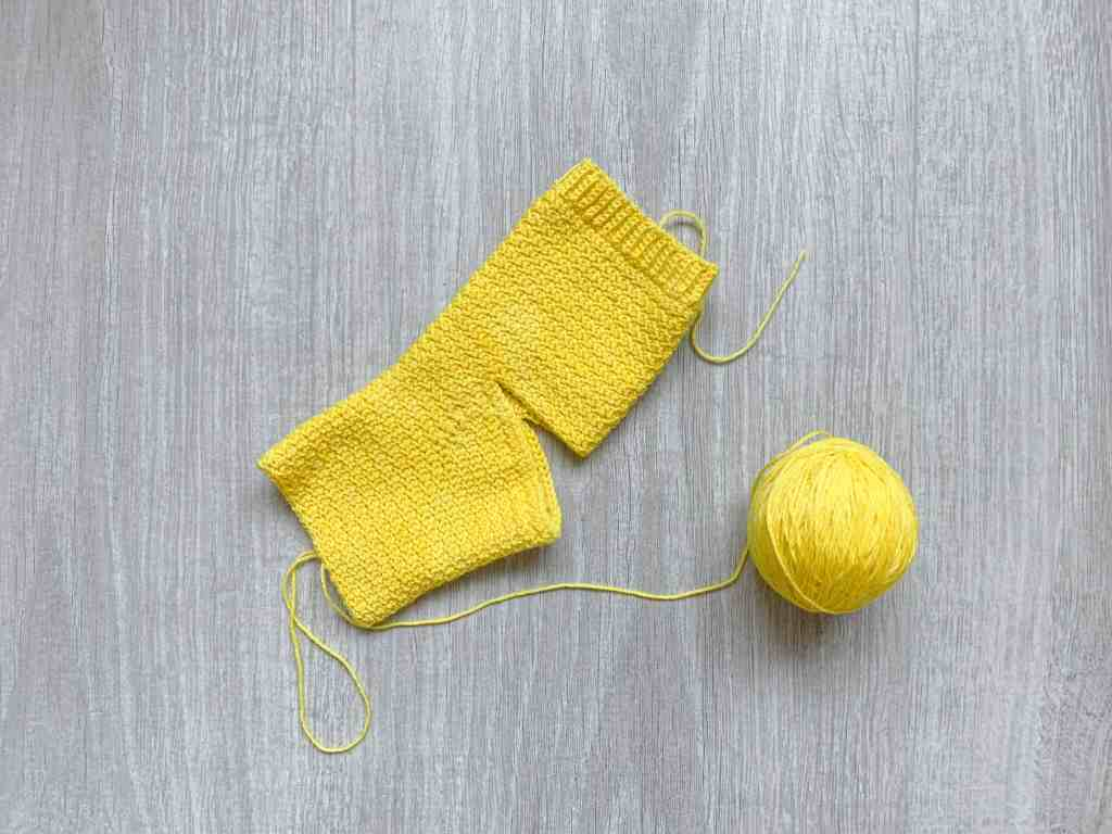 a yellow part made crochet sock lies on a grey wood grain surface with the ball of yarn still attached