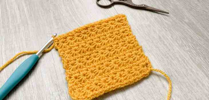 A yellow swatch of crochet star stitch lays at an angle on a grey wood grain surface with a turquoise crochet hook still attached and a pair of scissors off to the side