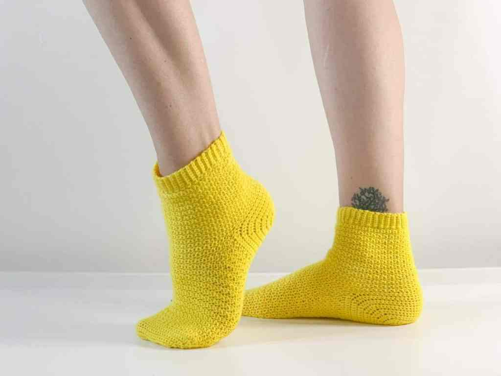 The side view of a somean's crochet sock clad feet with the front foot lifted on to tip toe