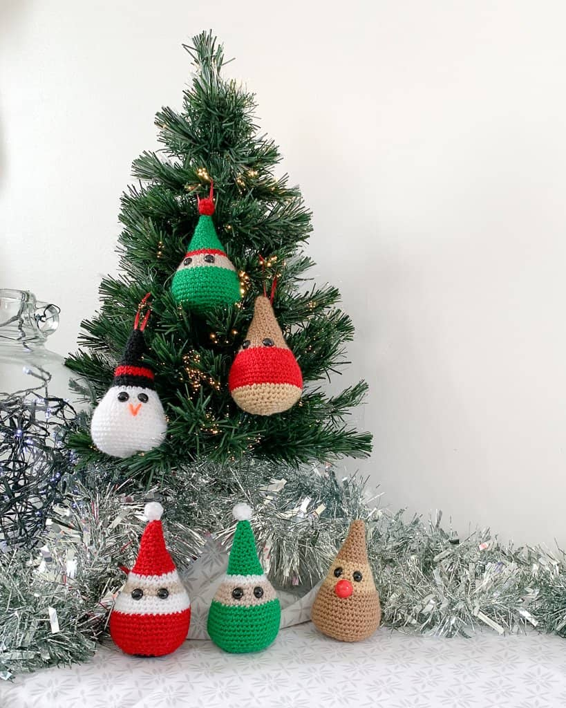 3 crochet Christmas decorations, including a Santa elf and rudolph gather round the bottom of a small christmas tree whilst a snowman elf and robin hang in the tree