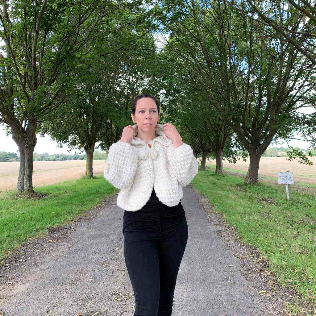 A woman wearing black jeans and a natural wool crochet hooded cape stands in the centre of a tree lined avenue with fields to either side. She holds the hood as if about to pull it up over her head