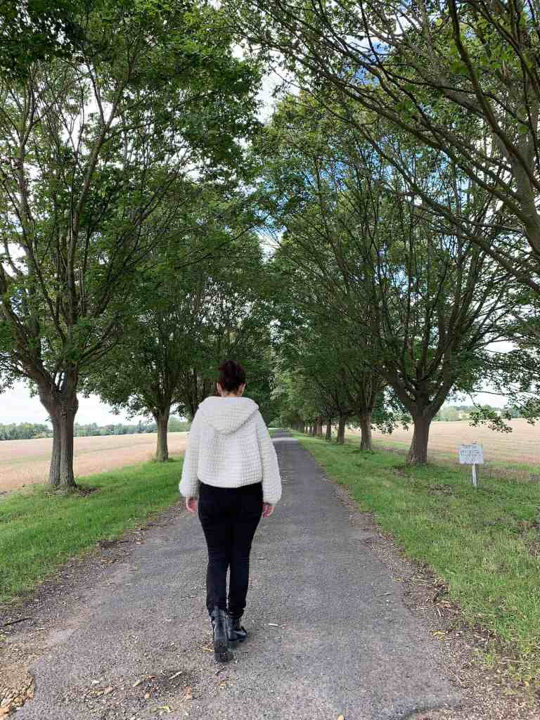 A woman wearing black jeans and a natural wool crochet hooded cape walks away from the camera down a tree lined avenue with fields to either side.