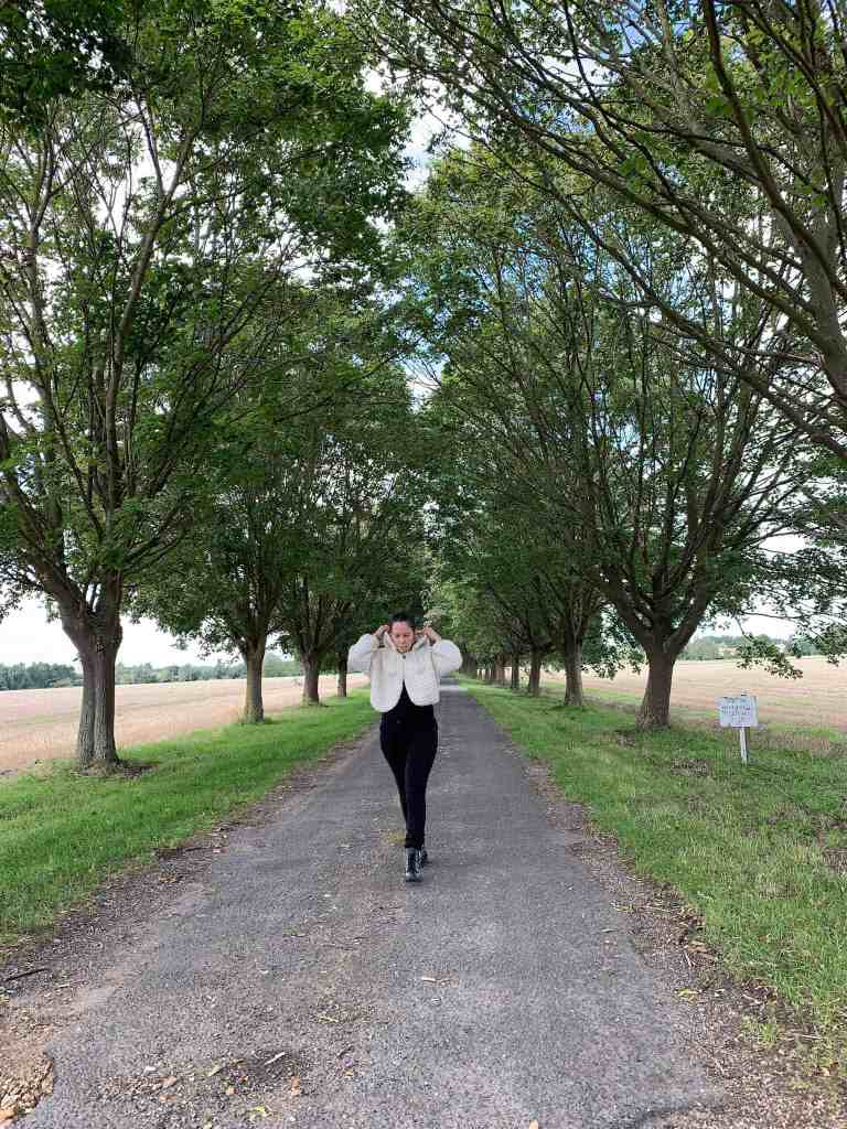 A woman wearing black jeans and a natural wool crochet hooded cape walks towards the camera down a tree lined avenue with fields to either side. She is pulling the hood up as she walks