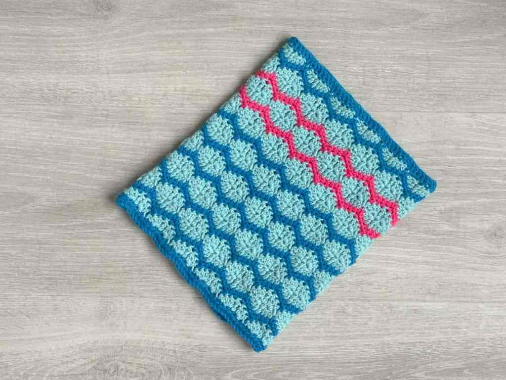 A Crochet snood made from rows of teal joined hexagons bordered with bright turquoise zig zags lies on a grey wood effect surface. Two of the stripes have been worked in neon pink and pop out of the image
