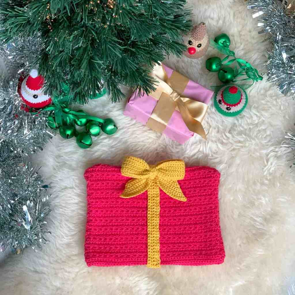 a pink crochet gift shaped christmas hat, with yellow ribbon and bow, lies on a sheepskin rug under a Christmas tree surrounded with green bells, tinsel, crochet character decorations and a gift wrapped in pink with a gold bow