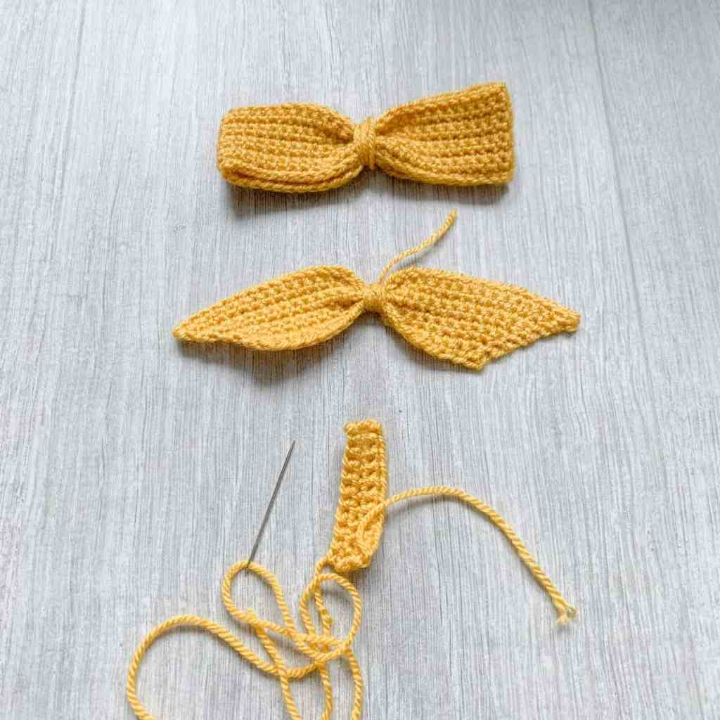 The 3 separate parts required to construct a crochet bow lie on a grey wood effect background with a needle attached to the tie section
