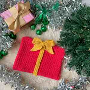 a pink crochet gift shaped christmas hat, with yellow ribbon and bow, lies on a sheepskin rug under a Christmas tree surrounded with green bells, tinsel and a gift wrapped in pink wrapping with a gold bow