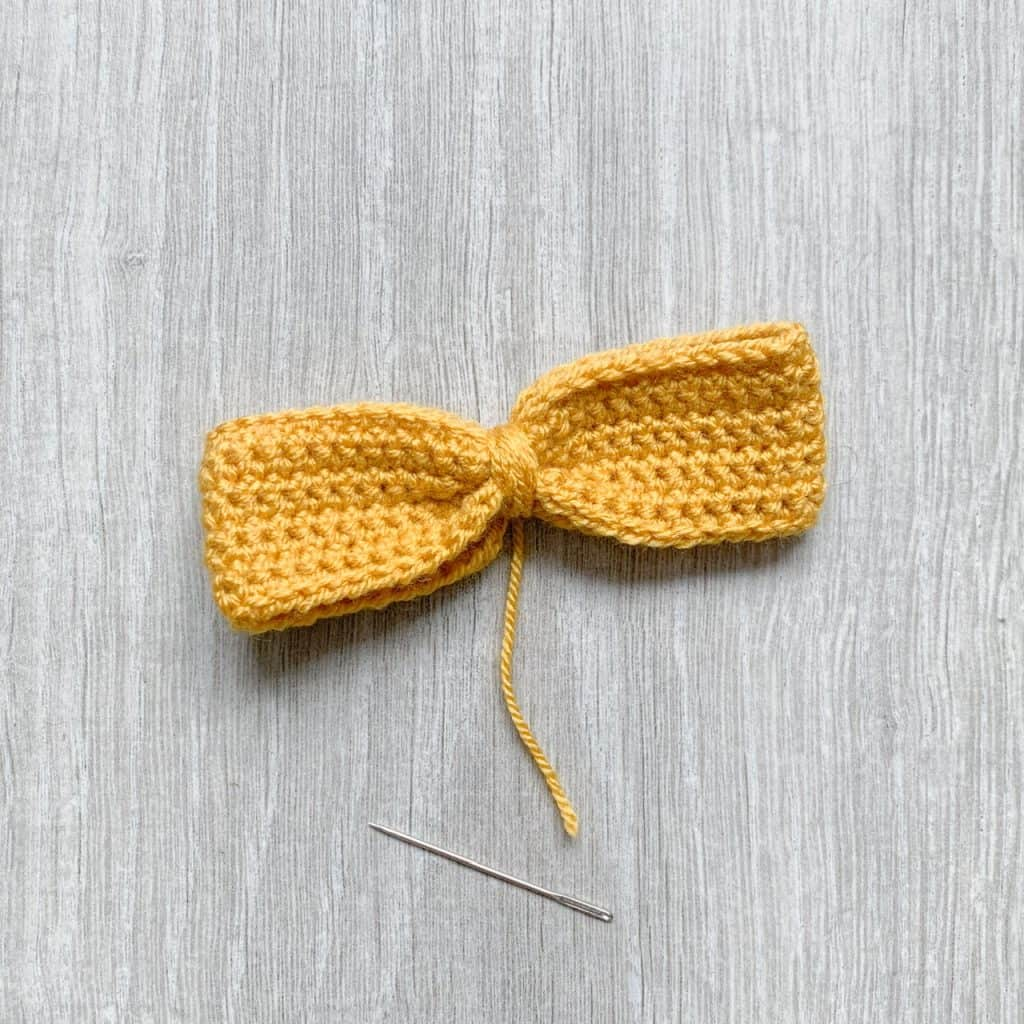 A yellow crochet bow lays on a grey wood grain surface with a yarn needle placed next to the yarn tail