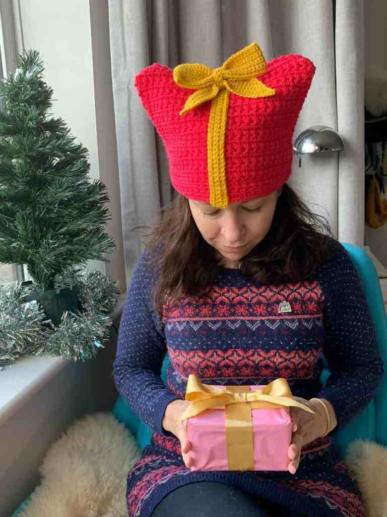 A woman sits on a chair by a window next to a christmas tree containing crochet character Christmas decorations. She is wearing a crochet hat made to look like a gift and holds a gift in her hands wrapped in pink paper and a gold bow. She has a string of tinsel round her neck wearing a christmas jumper