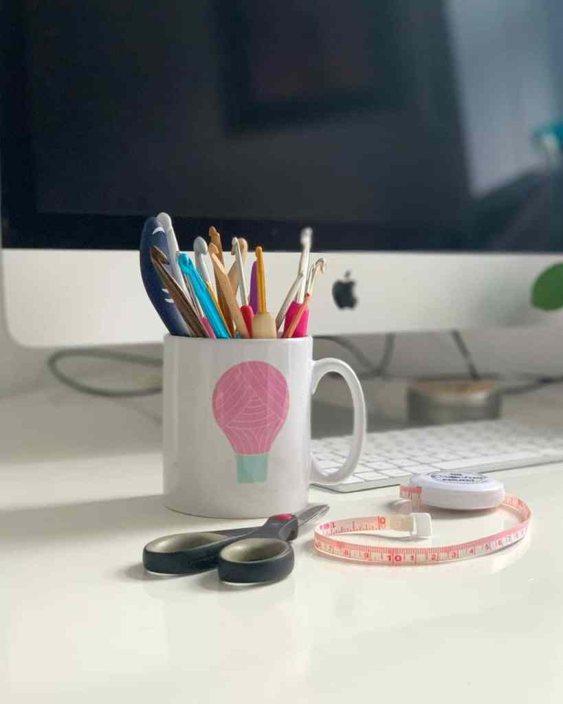A mug full of crochet hooks with the Dora does logo on the front sits on a white desk. A pair of scissors and a tape measure lay next to it, with a computer in the background