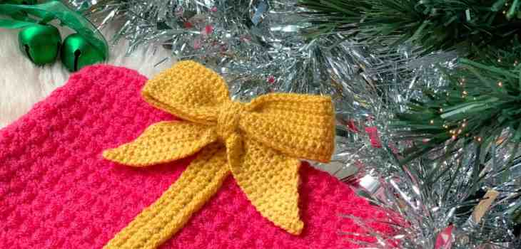A yellow crochet bow is attached to a pink crochet rectangle surrounded by tinsel, with branches of a christmas tree encroaching and some green bells are in the background