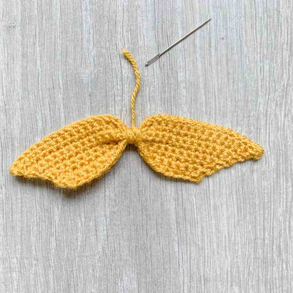 The ribbon section of a crochet bow lays on a grey wood effect surface with a yarn needle to the side