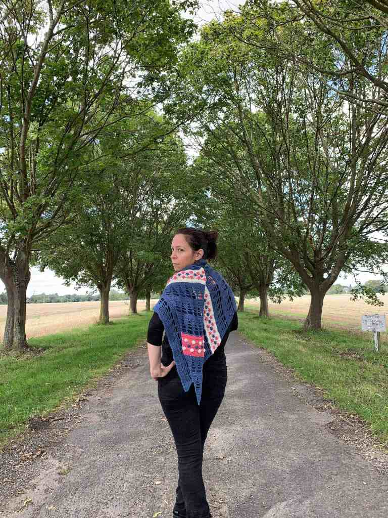 A woman stands in the centre of a tree lined avenue wearing all black with a blue, cream and pink crochet shawl wrapped around her shoulders. She has her hands on her hips and looks over her shoulder towards the camera