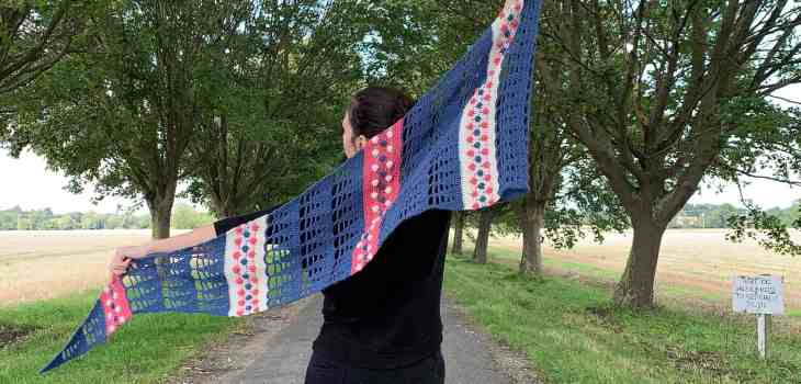 A woman stands in the centre of a tree lined avenue wearing all black. Her arms are outstretched holding either end of a blue, cream and pink crochet shawl which is flapping in the breeze. Her back is to the camera